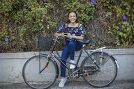 Portrait of smiling teenage girl with cell phone and bicycle - ZEF15653