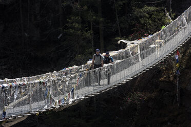 Nepal, Solo Khumbu, Everest, Sagamartha National Park, Two people crossing suspension bridge - ALRF01246
