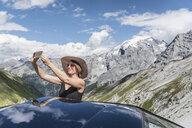 Woman taking selfie in front of mountains, Passo di Stelvio, Stelvio, Italy - CUF23372
