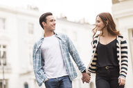 Couple walking in street face to face smiling - CUF23402