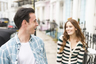 Couple in street face to face smiling - CUF23405