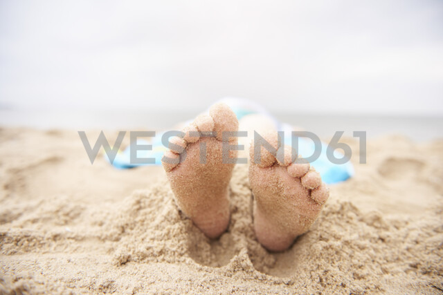 Child lying on sandy beach, view from feet - CUF23420