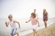 Family running along sandy beach - CUF23423