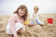 Children building sand castle on beach - CUF23426