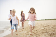 Family running along sandy beach - CUF23429