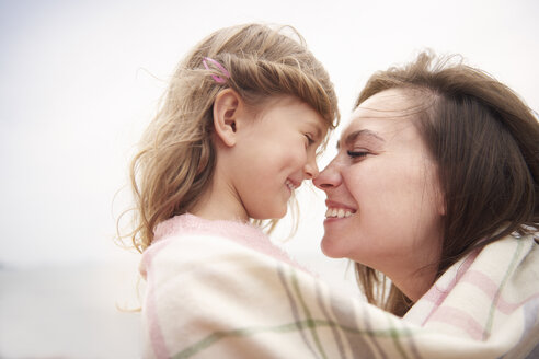 Happy mother and daughter wrapped in blanket, rubbing noses - CUF23438