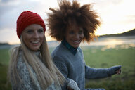 Portrait of two young women by sea at sunset - CUF23447