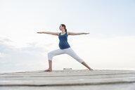 Pregnant woman on pier in yoga position, Majorca, Spain - CUF23468