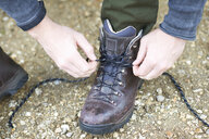 Cropped view of man tying shoe lace on hiking boot - CUF23477