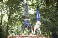 Couple in forest doing handstand on fallen tree - CUF23486