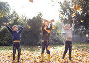 Three boys outdoors, throwing autumn leaves - CUF23504