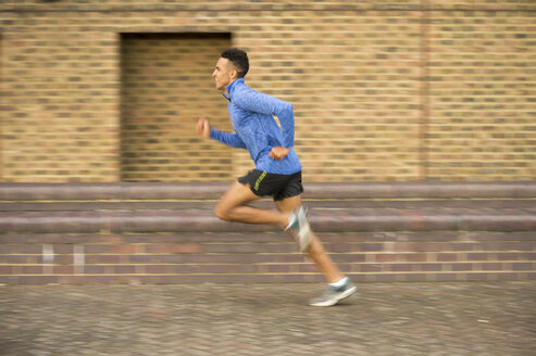 Man running past brick wall, Wapping, London, UK - CUF23519