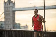 Man running by riverside, Tower Bridge in background, Wapping, London, UK - CUF23522
