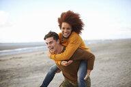 Couple playing piggyback on beach - CUF23537