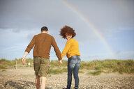 Couple walking on beach towards rainbow - CUF23540
