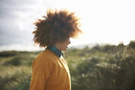 Woman with afro hair on grassy dune - CUF23543