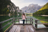 Woman leaning against wooden railing, Lago di Braies, Dolomite Alps, Val di Braies, South Tyrol, Italy - CUF23558