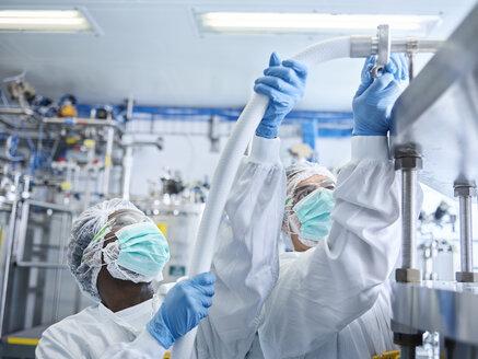 Chemical laboratory technicians fitting hose - CVF00724