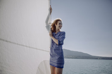 Smiling woman standing on a sailing boat - JLOF00048