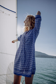 Smiling woman standing on a sailing boat - JLOF00054
