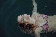 Carefree woman swimming in water - JLOF00057