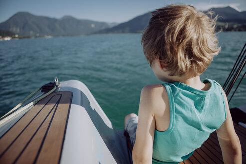 Boy sitting on a sailing boat - JLOF00069