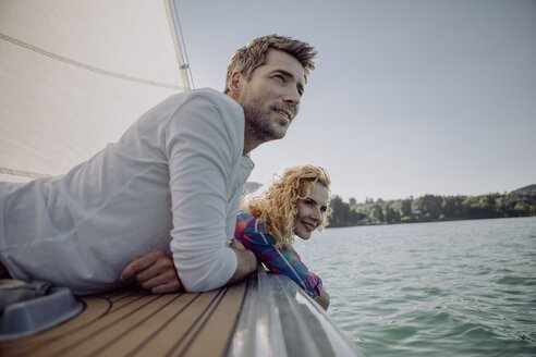 Smiling couple relaxing on a sailing boat - JLOF00078