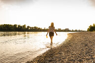 Young woman walking barefoot on riverside in the evening - UUF14036