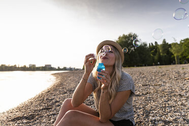 Blond woman blowing soap bubbles at riverside - UUF14039