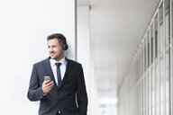 Young businessman outside office listening to smartphone music on headphones - CUF23635