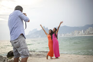 Rear view of man photographing two young women on Ipanema beach, Rio De Janeiro, Brazil - CUF23685