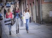 Three female friends strolling along street with shopping bags, Cagliari, Sardinia, Italy - CUF23697