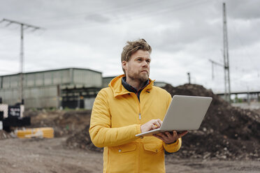 Man holding laptop, construction site in the background - KNSF03977