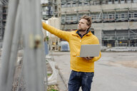 Man holding laptop, construction site in the background - KNSF03980