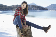 Portrait of young woman sitting on tree stump at snow covered lakeside, German Alps, Germany - CUF23806