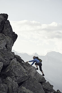 Mature man climbing up rocks, Valais, Switzerland - CUF23890