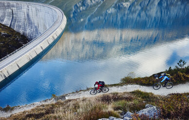 Mountain bikers by reservoir, Valais, Switzerland - CUF23914