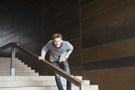 Portrait of young man carrying digital tablet on city stairway - CUF23935