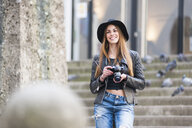 Young stylish woman photographing on city steps with SLR camera - CUF23950