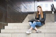 Young woman using laptop on city stairway - CUF23956