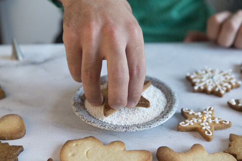 Man's hand decorating Christmas Cookie, close-up - SKCF00487