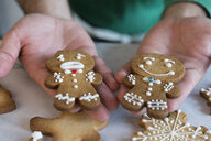 Man's hands holding two different Gingerbread Men, close-up - SKCF00490