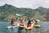 Rear view of four female friends celebrating in kayaks on  Lake Atitlan, Guatemala - CUF24067