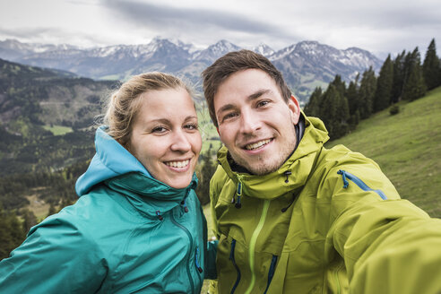 Young hiking couple taking self portrait, on the way down Zinken mountain, Oberjoch, Bavaria, Germany - CUF24106