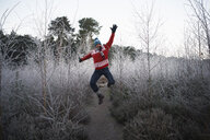 Man jumping in rural winter scene - CUF24112