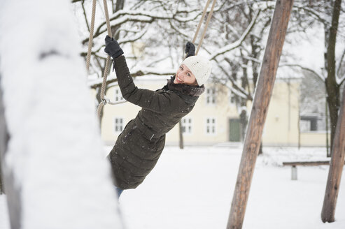 Mid adult woman swinging on tree swing, in snow covered rural scene - CUF24154