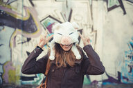 Portrait of mid adult woman hiding face with pig fur hat - CUF24274