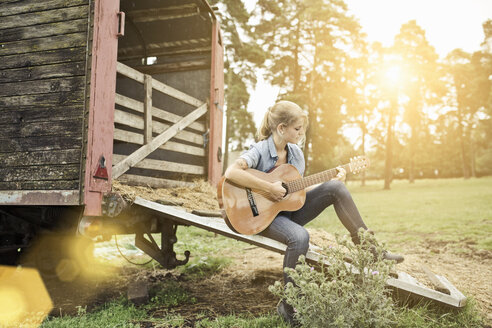 Portrait of young woman, sitting on wooden cart, playing guitar - CUF24283