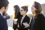 Group of friends laughing and drinking at party - CUF24307