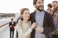 Heterosexual couple laughing together at party - CUF24319